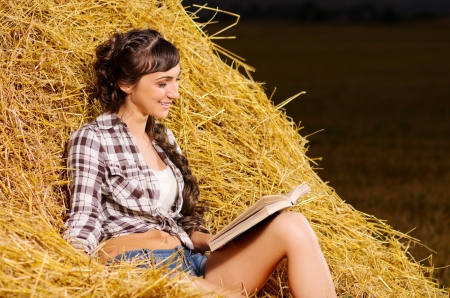 Young girl reading book on haystack photo
