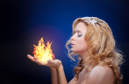 Frozen girl hold a falme in palms (little flame) photo