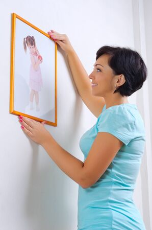 Smiling woman hanging up image of little girl photo