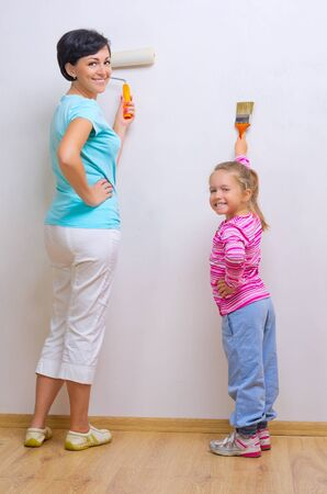 Happy woman and her daughter doing home repair photo