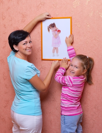 Woman and her daughter hanging up photography photo