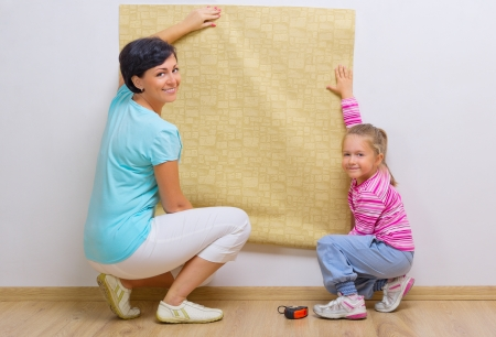 Happy woman and her daughter with wallpaper roll photo