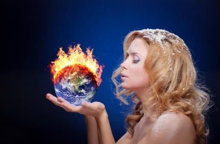 Bevroren meisje met brandende aarde wereldbol (west halfrond) in palmen (elementen geleverd door NASA) - versie zonder gloeiende