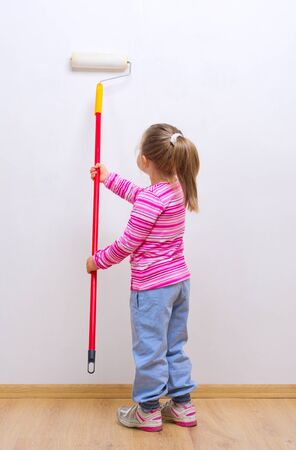 Little girl with painting roller photo