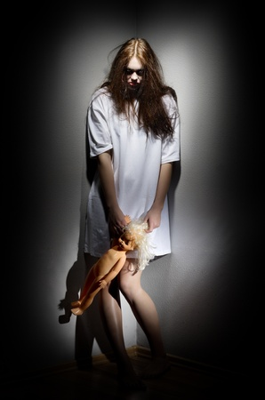 Zombie girl holding plastic doll photo
