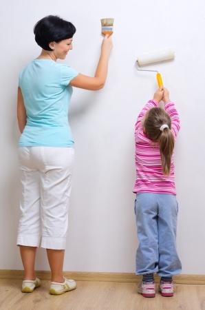 madre trabajadora: Mujer joven sonriente y ni�a con las herramientas de pintura
