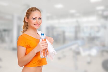 Young smiling woman with water bottle and towel photo