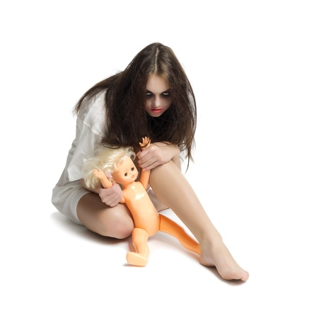 Zombie girl with plastic doll photo