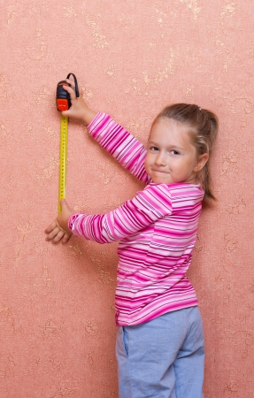 manual measuring instrument: Little smiling girl with measurement tape