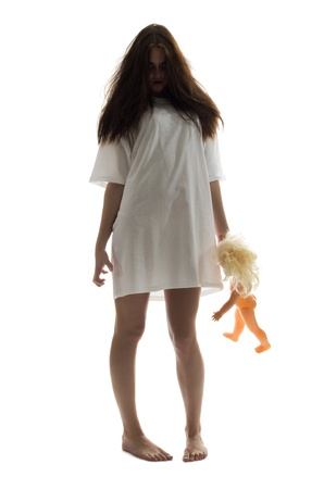 Zombie girl with plastic doll isolated photo