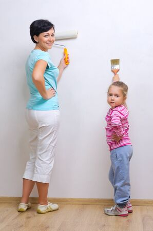 Young woman with little girl doing home repair photo