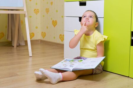 reflects: Little girl reading box in a home Stock Photo