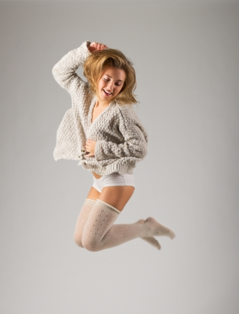 Jumping young girl on grey background photo