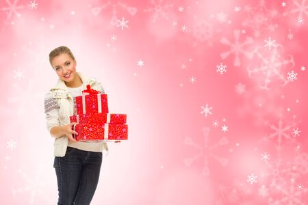 Young girl with gift boxes on winter background photo