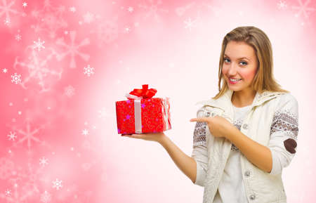 Young girl with gift box on red winter background photo