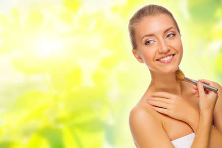 Young healthy woman with makeup brush on spring background photo