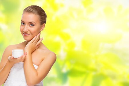 Young healthy girl with body cream on spring background photo