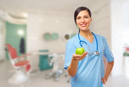 Jonge arts met groene appel op medische kantoor