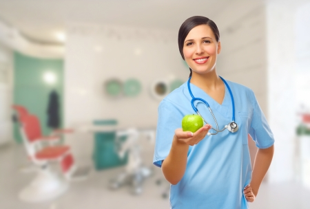 medical personnel: Young doctor with green apple on medical office Stock Photo