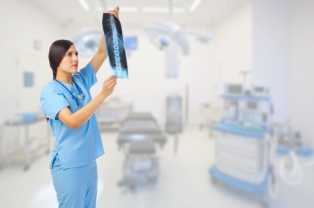 Young doctor looking to x-ray on medical office Stock Photo - 17786574