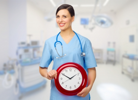 Young doctor with clock at medical office photo