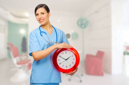 Smiling doctor with clock at medical office photo