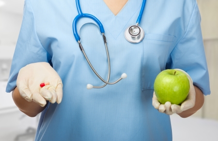 Doctor with pill and green apple Imagens