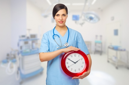 Doctor with red clock at medical office Stock Photo - 18466129