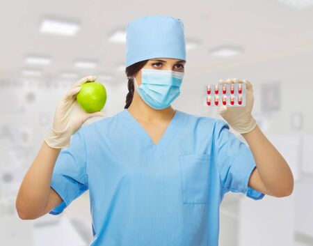 Doctor with apple and pills at lab photo