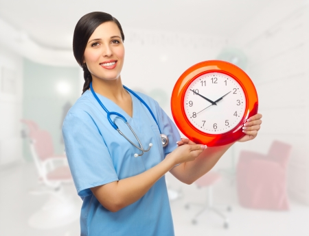 Doctor with clock at medical office Stock Photo - 18735867