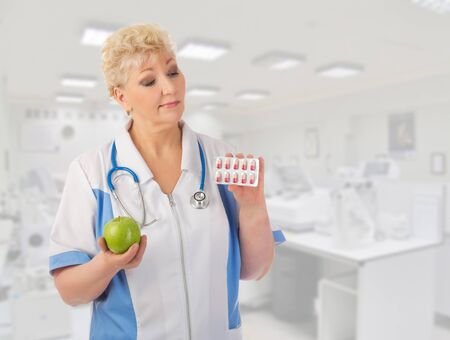 Mature doctor with apple and pills at lab photo