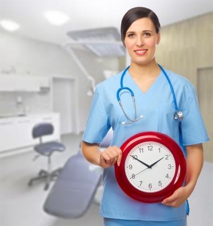 Doctor with clock at medical office Stock Photo - 19664279