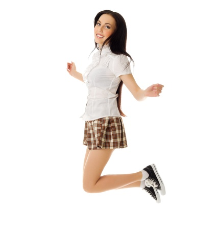 Jumping school girl in plaid skirt and sneakers isolated photo
