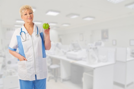 Mature doctor with apple at lab photo