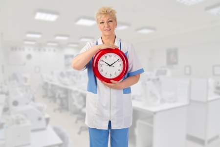 Mature doctor with clock at medical office Stock Photo - 20144616
