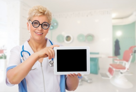 Mature doctor with funny glasses and tablet PC at medical office photo