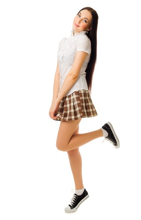 Young jumping girl in plaid skirt isolated photo