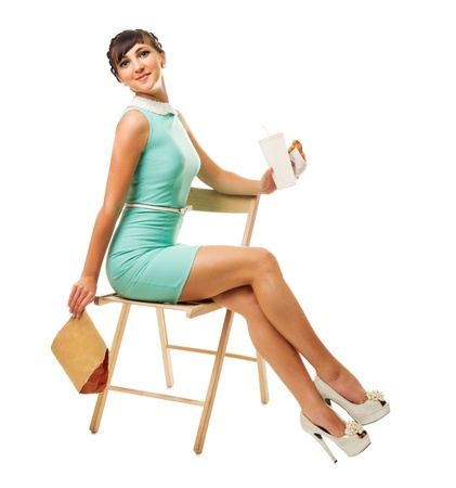 Glamorous girl in turquoise dress sitting on chair holds snacks isolated photo