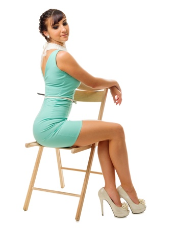 Glamorous girl in turquoise dress sit on chair isolated Stock Photo