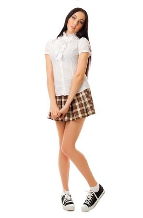 Modest school girl in plaid skirt isolated photo
