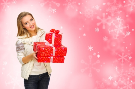 Young girl with gift boxes on red snowy background photo