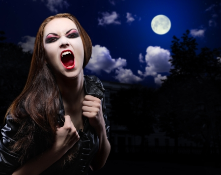 Vampire girl on night sky background photo