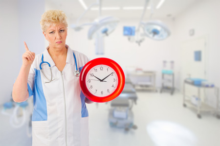 Mature furious doctor with clock at medical office photo