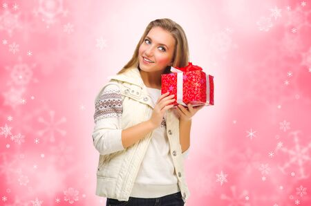 Young girl with gift box on winter background photo