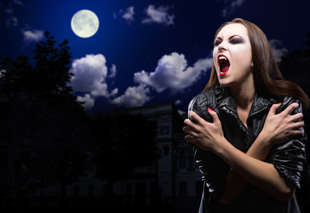 Vampire girl on night sky with moon Stock Photo