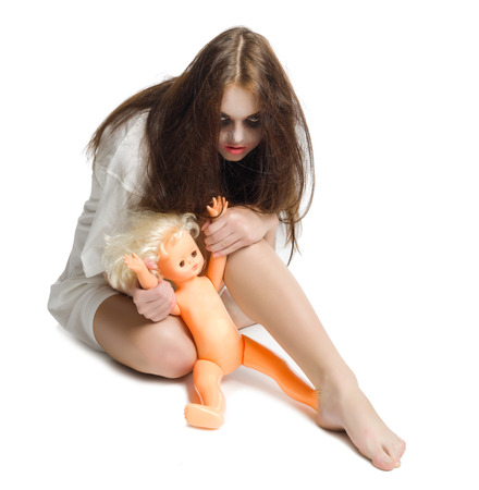 Zombie girl with plastic doll isolated on white photo