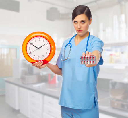Young doctor with clock and pills at lab photo
