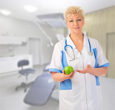 Mature doctor with apple at medical office photo