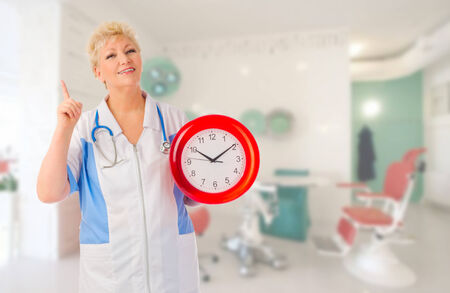 Mature doctor with clock at medical office photo