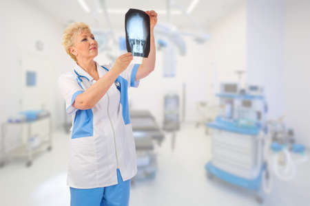 Mature doctor with x-ray at medical office photo